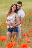 Smiling couple in poppies plants Royalty Free Stock Photography