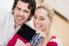 Smiling couple pose for a selfie on their mobile Stock Image