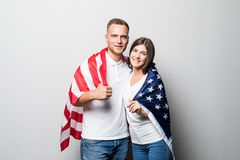 Smiling couple in love posing with USA flag isolated on gray background. Happy handsome boy in white shirt and pretty girl with royalty free stock photography