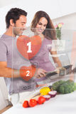 Smiling couple preparing dinner using futuristic interface. In the kitchen at home Royalty Free Stock Images