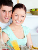 Smiling couple preparing spaghetti in the kitchen Stock Photo