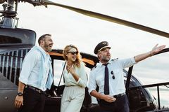 Smiling couple by a private helicopter with pilot. Beautiful couple standing by helicopter with pilot pointing at something interesting at a distance. Smiling royalty free stock image