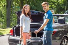 Smiling Couple Putting Luggage In A Car Trunk. Portrait Of Young Happy Couple Putting Luggage In A Car Trunk Royalty Free Stock Photography