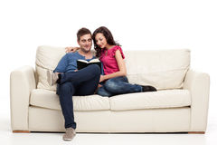 Smiling couple reading from book Stock Photos