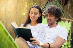 Smiling couple reading book together outdoors Stock Photography