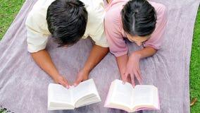 Smiling couple reading books Stock Photos