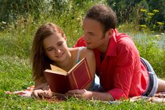 Smiling couple reading and relaxing at the park. Royalty Free Stock Photos