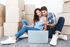 Smiling couple ready to move out. Looking for a new apartment on their laptop Stock Image