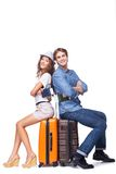 Smiling couple is ready to travel. Happy couple is ready to travel, sitting on luggage and holding passports, isolated on white background Royalty Free Stock Photography
