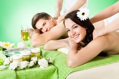 Smiling couple receiving shoulder massage at beauty spa Royalty Free Stock Images