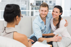 Smiling couple reconciling at therapy session Stock Photo