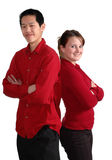Smiling couple in red. Couple back to back in red shirts; isolated on white Royalty Free Stock Photography