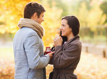 Smiling couple with red gift box in autumn park Stock Image