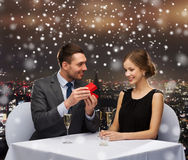 Smiling couple with red gift box at restaurant Royalty Free Stock Photography