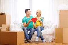 Smiling couple with red heart on sofa in new home Royalty Free Stock Images