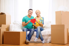 Smiling couple with red heart on sofa in new home Royalty Free Stock Image