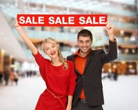 Smiling couple with red sale sign Royalty Free Stock Photos