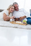 Smiling couple with red wine and food while lying on rug Royalty Free Stock Photo