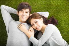 Smiling Couple Relaxing on Green Grass Stock Photo