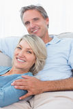 Smiling couple relaxing at home Royalty Free Stock Images
