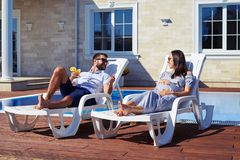 Smiling couple relaxing near pool Royalty Free Stock Image