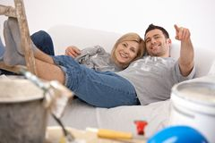 Smiling couple relaxing after painting Royalty Free Stock Photos