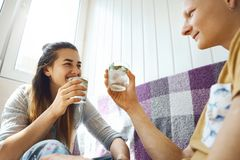 Smiling Couple relaxing on sofa on balcony and holding glasses with cold mint lemonade. Enamoured young couple spending time together at home at sunny day and stock image