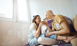 Smiling Couple relaxing on sofa on balcony and holding glasses with cold mint lemonade. Enamoured young couple spending time together at home at sunny day and stock images