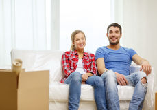 Smiling couple relaxing on sofa in new home. Moving, home and couple concept - smiling couple relaxing on sofa in new home royalty free stock photos