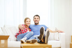 Smiling couple relaxing on sofa in new home. Moving, home and couple concept - smiling couple relaxing on sofa in new home stock photography