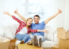 Smiling couple relaxing on sofa in new home. Moving, home and couple concept - smiling couple relaxing on sofa in new home stock photo