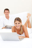 Smiling couple relaxing on their bed Royalty Free Stock Photography