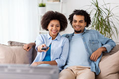 Smiling couple with remote watching tv at home Royalty Free Stock Photo