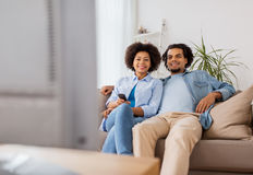 Smiling couple with remote watching tv at home Stock Photo