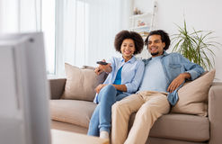 Smiling couple with remote watching tv at home Royalty Free Stock Photos