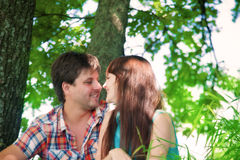Smiling couple resting near a tree Royalty Free Stock Images