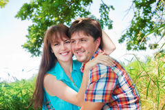 Smiling couple resting near a tree Stock Images