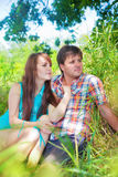 Smiling couple resting near a tree Stock Photos