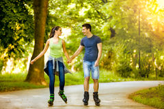 Smiling couple riding rollerblades Stock Photo