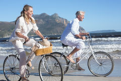 Smiling couple riding their bikes on the beach Stock Photography