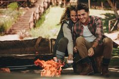 Smiling couple roasting sweets on bonfire. Smiling young couple roasting sweets on bonfire at campsite. Man and women having roasted marshmallows on camping Royalty Free Stock Image