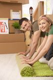 Smiling couple roll out carpet together Royalty Free Stock Images