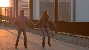 Smiling couple on rollerblades.