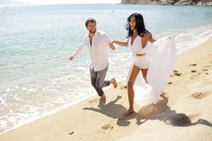 Smiling couple run on beach, in wedding clothing, enjoying in honeymoon, in summer time, sunny day, holiday, Greece. stock photo