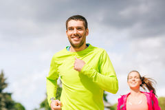 Smiling couple running outdoors Royalty Free Stock Photo
