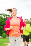 Smiling couple running outdoors Stock Image