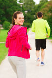 Smiling couple running outdoors Royalty Free Stock Images