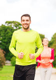 Smiling couple running outdoors Stock Photo