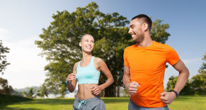 Smiling couple running over summer park background. Fitness, sport, exercising and healthy lifestyle concept - smiling couple running or jogging over summer park Stock Image