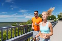 Smiling couple running at summer seaside Royalty Free Stock Photos